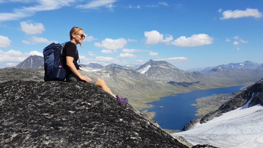 Christine sitter på fjellet og nyter utsikten over fjell og vann i Jotunheimen.